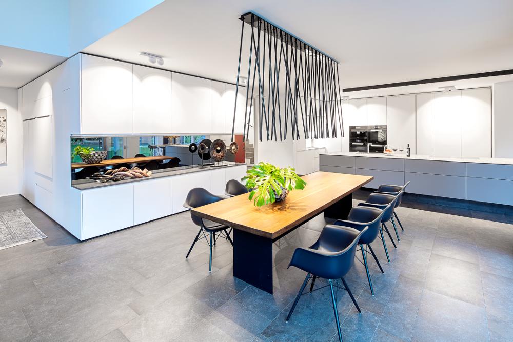Esstischbeleuchtung mit der Leuchte peled von Viabizzuno im Vordergrund und Küchen- und Wandbeleuchtung mit inVision Leuchte von O/M und Marbul von Modular im Hintergrund