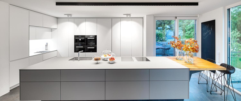 Perfekte Küchenbeleuchtung mit inVision Aufbauprofil von O/M Light über der Kücheninsel und Marbul Aufbauleuchten von Modular als Schrankbeleuchtung